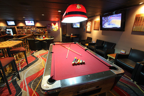 A billiards table with a rack of balls and two cue sticks