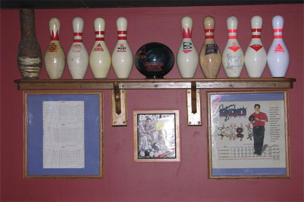 Bowling pins on wall and a picture Jeremy Sonnenfeld and his score sheet from his 900 series