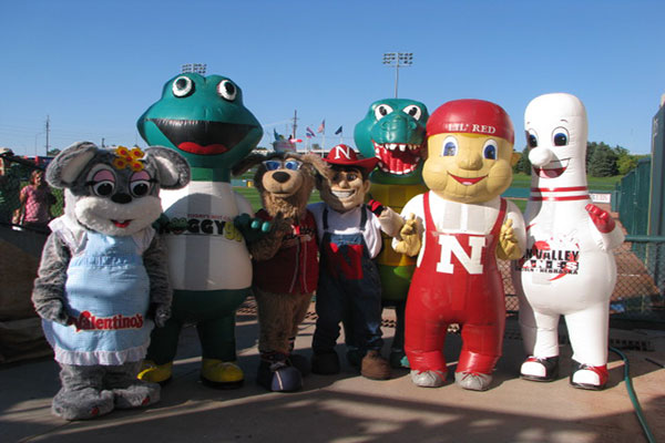 Large blow-up bowling pin mascot standing with other mascots, including Herbie Husker and Lil Red